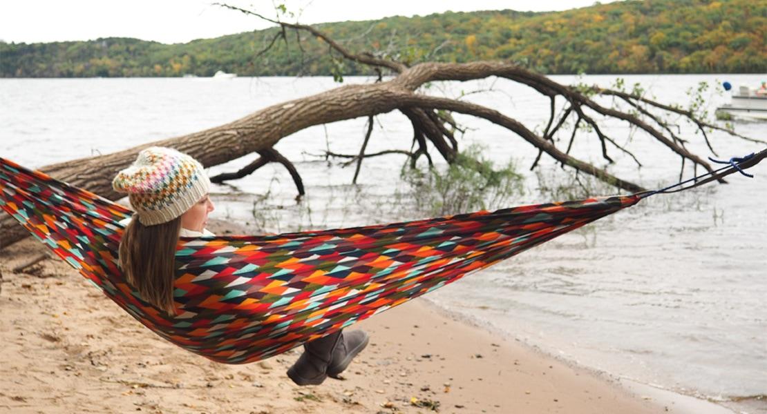 woman lying in a coalatree hammock near a river