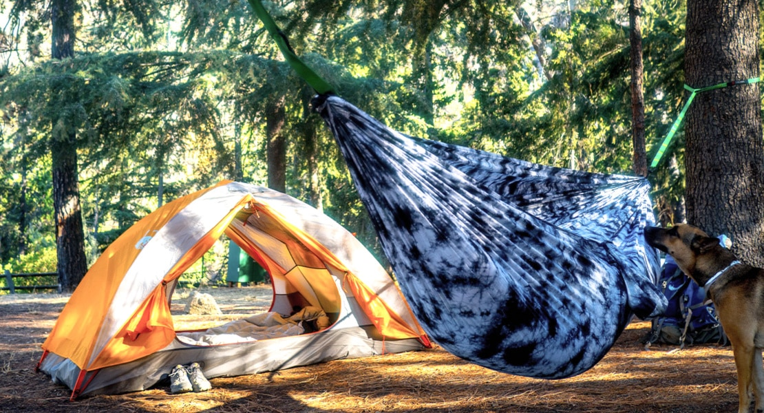 Grand Trunk Goods hammock near an open tent during the day at a campground