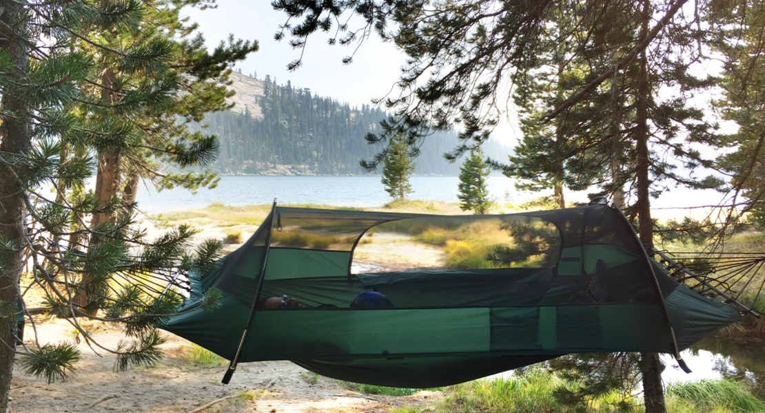 lawson blueridge camping hammock hung between trees near a lake with a person inside