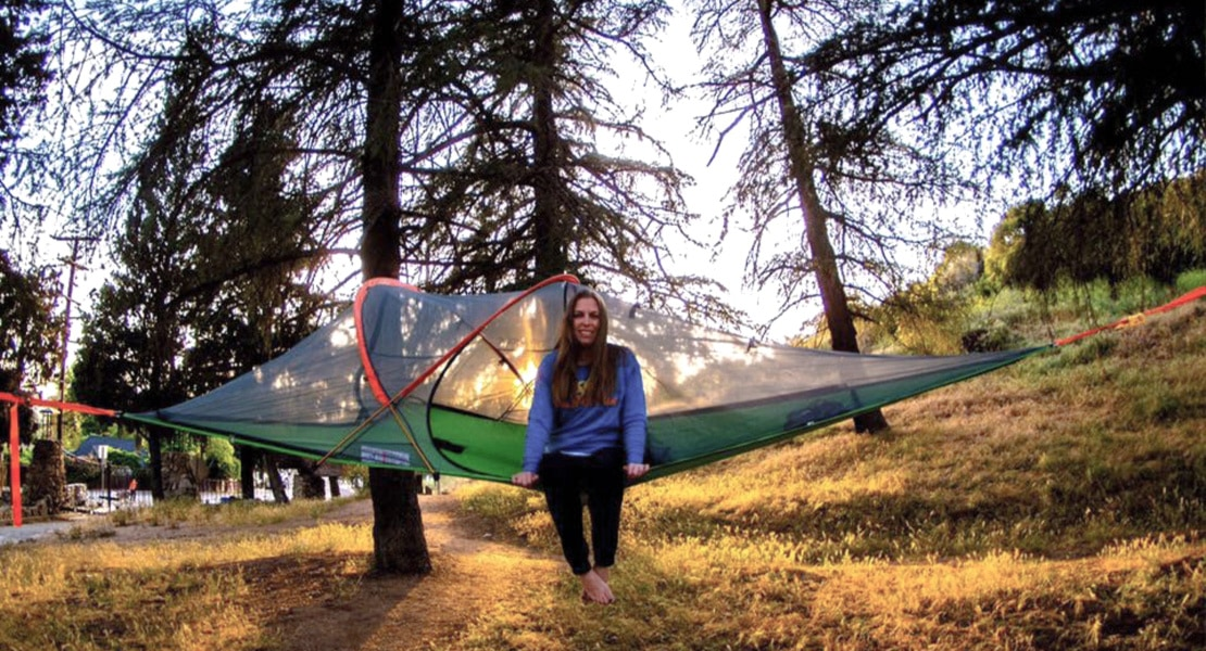 woman sitting upright in a tentsile camping hammock at dusk