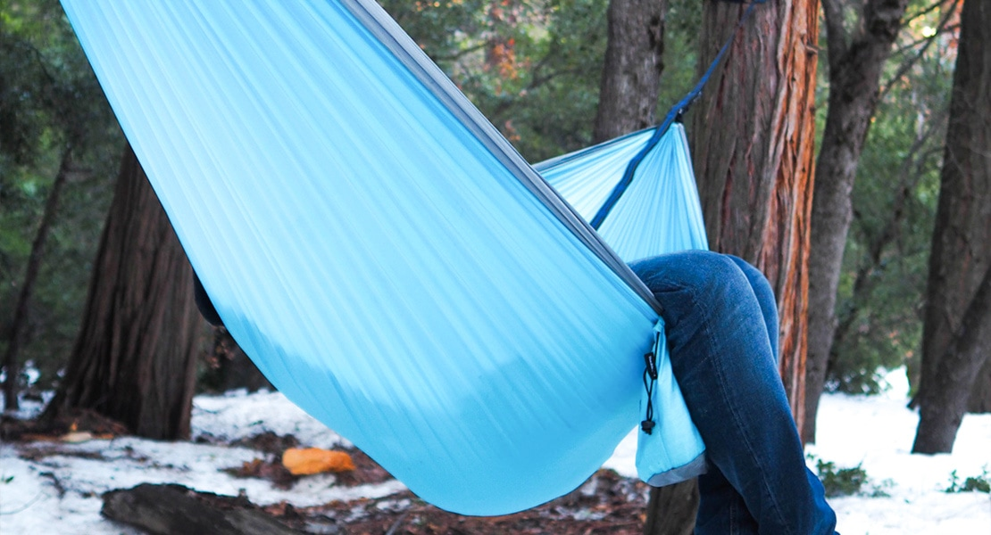 blue wiseowl outfitters hammock hung from a tree