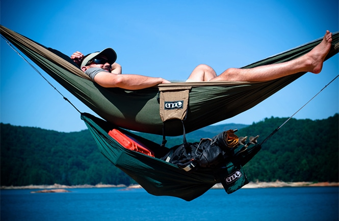 ENO Underbelly Gear Sling with a man in a hammock at a lake