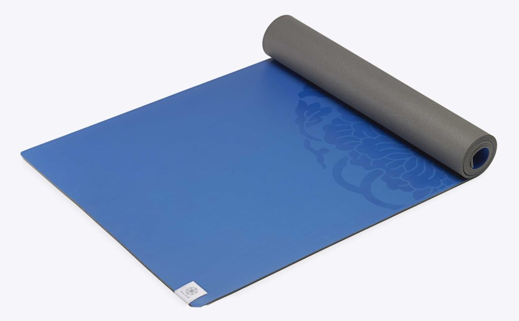 blue yoga mat lying on the floor half rolled up