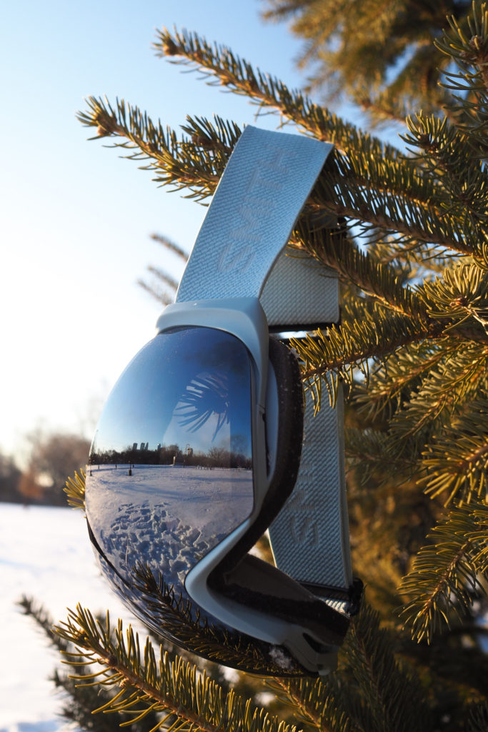 Smith I/O Mag Snow Goggles with blue strap hanging from a tree