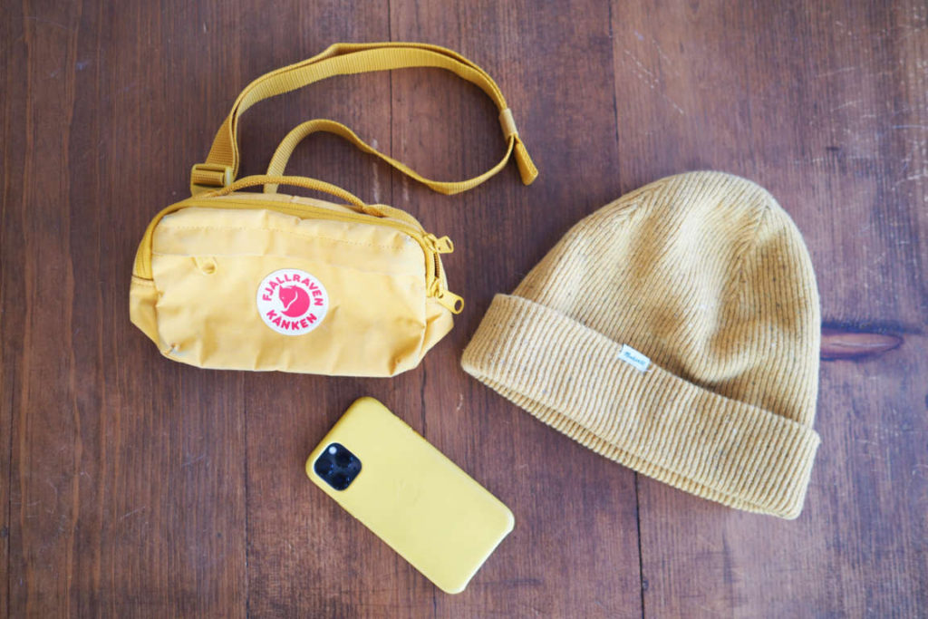 Fjallraven Kanken Hip Pack next to a beanie and iphone
