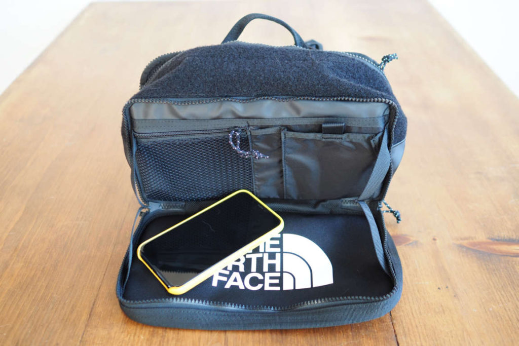 The North Face Explore BLT Fanny Pack front pocket open with iphone to show size and scale