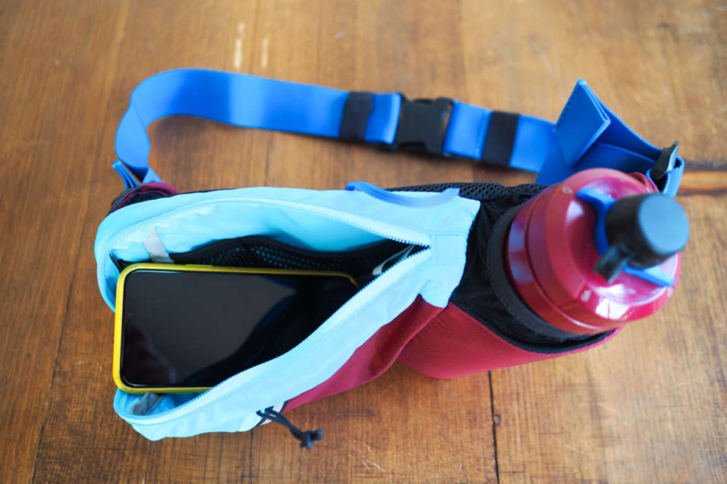 Camelbak Podium Flow Belt fanny pack with an iphone showing size and scale