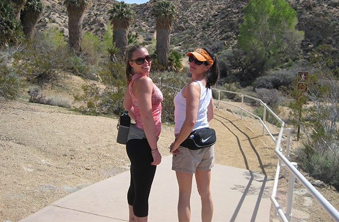 two girls wearing fanny packs hiking in joshua tree national park